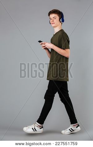 Portrait of a confident male teenager wearing t-shirt listening to music with headphones while walking and holding mobile phone isolated over gray background