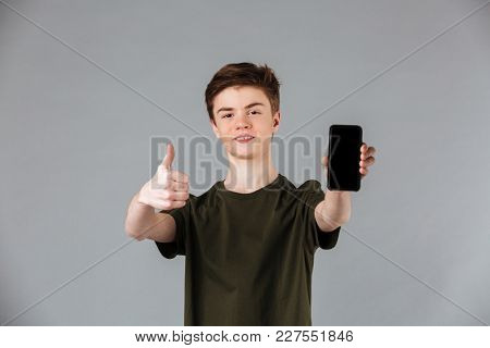 Portrait of a happy male teenager wearing t-shirt showing blank screen mobile phone and giving thumbs up isolated over gray background