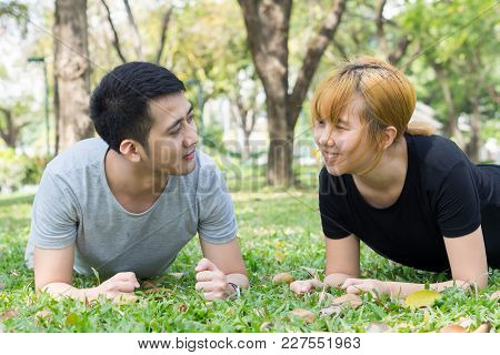 Asian Sweet Couple Exercising Together With Smile On Their Faces On Soft Grass Encircle With Nature