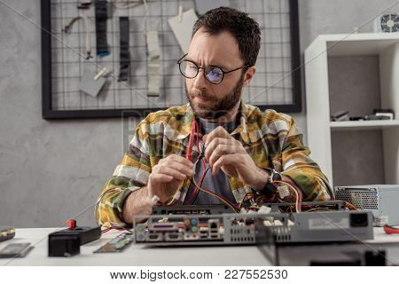 View Of Man Using Multimeter While Fixing Pc