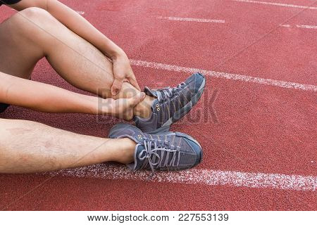 Sports Man Runner With Injured Ankle While Training In The Stadium