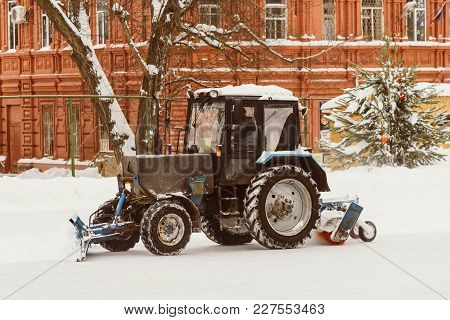 A Tractor With Brushes Removes Snow On The Rink