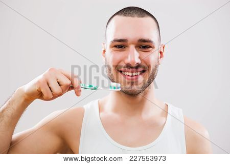 Portrait Of Young Man Who Is Holding Toothbrush.