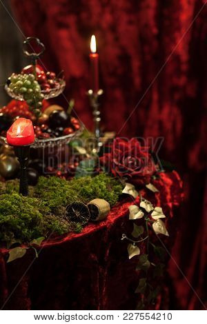 Dark Still Life In Red Tones With Candles, Moss And Roses. Vertical Frame