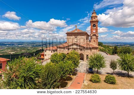 Old catholic church under beautiful blue sky with white clouds in small town of Diano d'Alba in Piedmont, Northern Italy.