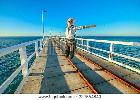Western Australia Travel Freedom Concept. Happy Caucasian Woman Jumping At Busselton Jetty In Bussel