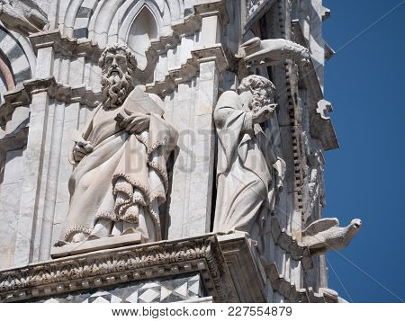 Exterior Of Siena Cathedral With Scupltutes Of Philosophers, Gargoyles And Other Intricate Decoratio