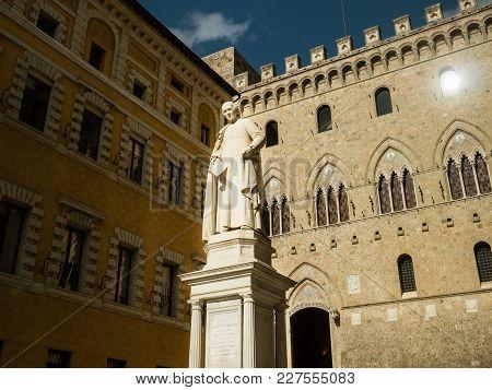 Statue Of Sallustio Bandini In Front Of The Palazzo Salimbeni Siena, Italy.