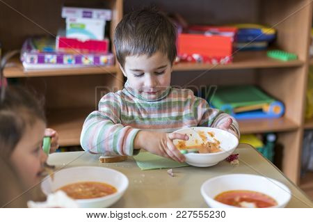 A Boy At The Age Of 5 Years Eating Soup In The Kindergarten