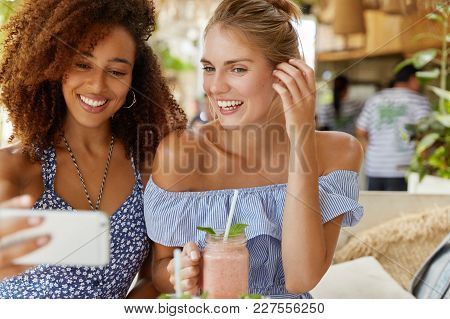 Smiling Cheerful Female Models Wear Fashionable Clothes, Pose For Making Selfie And Drink Tasty Smoo