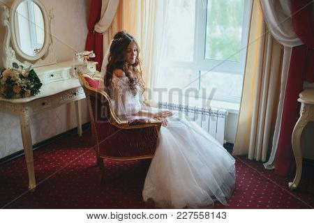 The Bride Posing On A Red Chair In The Hotel