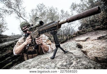 Private Military Contractor Pmc Sniper In Baseball Cap With Assault Rifle In The Rocks