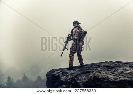 Private Military Contractor Pmc In Baseball Cap With Assault Rifle In The Rocks