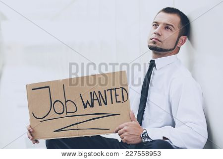 Unemployed Young Man Is Sitting With A Sign Job Wanted.