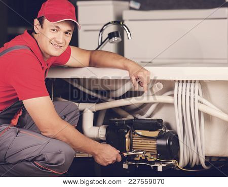 Image Of Young Pretty Plumber At Work.