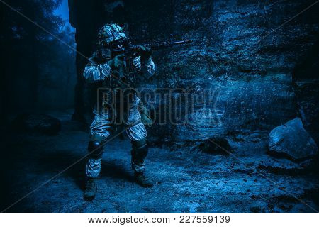 Us Marine Corps Soldier In Action Among The Rocks Under Cover Of Darkness. Dark Gloomy Night