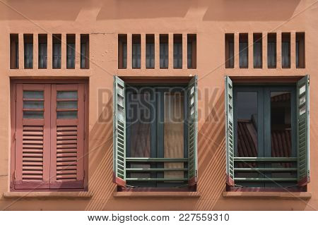 Building Wall With One Closed And Two Open Window Shutters In Chinatown Of Singapore City