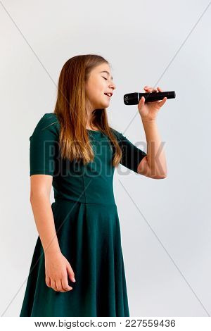 A Portrait Of A Girl Singing With A Microphone