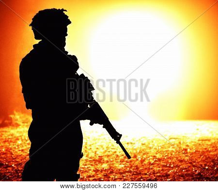 Black Silhouette Of Soldier On The Nuclear Explosion Background. Back Light, Cropped, Toned And Colo