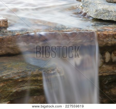 Single Sheet Of Water Flowing Over A Small And Rocky Waterfall