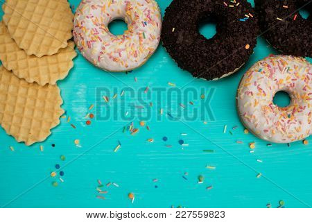 Four Donuts, Chocolate And With White Cream And Wafers Lie In A Semicircle On A Wooden Turquoise Bac