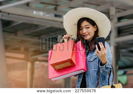 Cheerful Asian Young Woman Making Selfie Photo On Mobile Smart Phone With Shopping Bags In Big City,