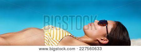 Beach vacation woman sun tanning bikini wearing sunglasses for solar protection eye care. Young girl lying down sunbathing relaxing. Skincare UV sun shade banner panorama.
