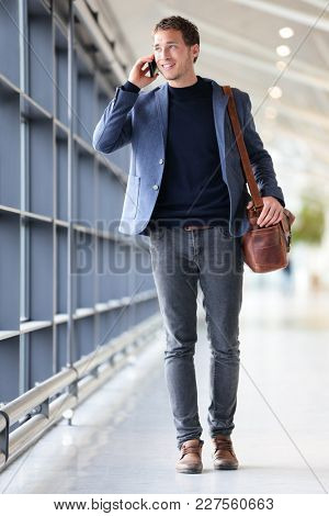 Urban business man talking on smart phone traveling walking inside in airport. Casual young businessman wearing suit jacket and shoulder bag. Handsome male model in his 20s. poster