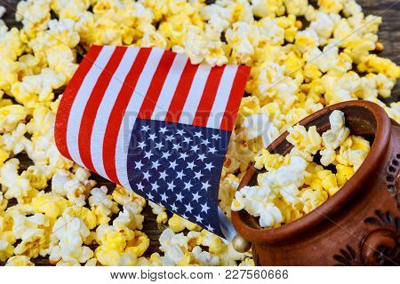 Salty Popcorn In A Wooden Cup Is On A White Table. American Flag Flying, Flag Usa Popcorn Lies Aroun