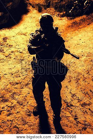 Black Silhouette Of Soldier At Night. View From Above, Toned And Colorized