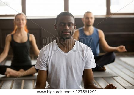 Young Black Man And A Group Of Sporty People Practicing Yoga Lesson With Instructor, Sitting In Sukh