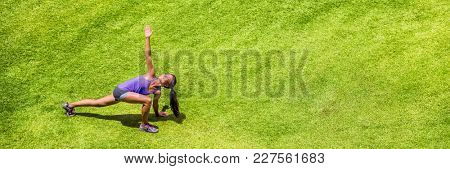 Fitness woman stretching yoga exercises banner panorama. Runner girl doing warm-up twisted twist high lunge stretch Parivrtta Anjaneyasana. Panoramic crop with green grass park texture.
