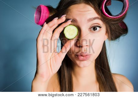Cute Young Girl Wants To Look Good, On The Head Of The Curler, Keeps The Cucumber For Moisturizing T