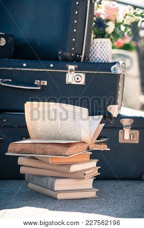 A Pile Of Aged Books On The Floor With Old Suitcases Stacked In The Background, One Book Open By The