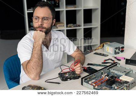 Pensive Repairman With Nand On Chin Using Multimeter  While Fixing Hard Disk Drive