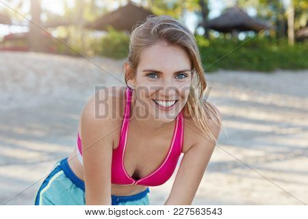 Positve Active Female With Broad Smile, Leans Over, Has Rest After Physical Exercise, Wears Sporty C