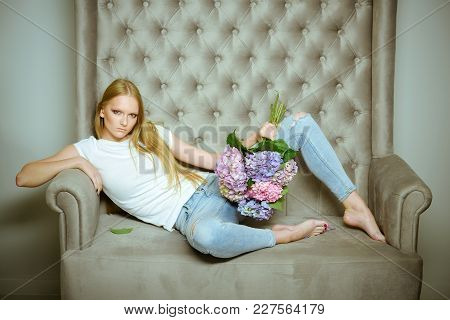 Woman With Hydrangea Flowers Relax On Sofa. Girl With Blond Hair, Makeup Face Hold Hortensia Bunch.
