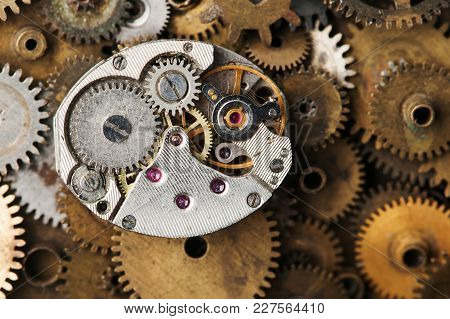 Vintage Clock Mechanism Close-up. Aged Hand Watches Parts On Bronze Gears Background.
