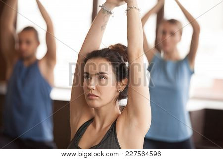 Portrait Of Yogi Woman And A Group Of Young Sporty People Practicing Yoga Lesson, Standing In Warrio