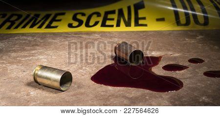 Pistol Brass And Blood On A Brown Tile Floor With Police Tape Behind