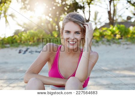Healthy Young Female Sport Runner In Sporty Clothes, Smiles Broadly, Sits Against Beach Background A