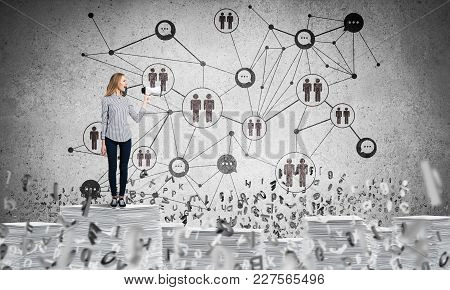 Woman In Casual Wear With Speaker In Hand Standing Among Flying Letters With Social Network Structur