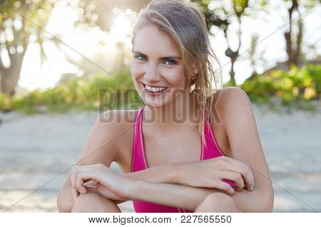 Young Positive Pretty Female Runner Recreats After Hard Workout At Seaside, Has Fit Body, Joyful Exp