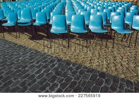 Blue Plastic Chairs, Empty And Arranged For The Spectacle Of The Public, On Stone Floor