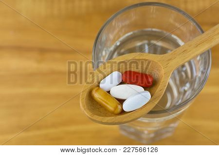 Dietary supplements in wooden spoon, royal Jelly in soft gel capsule, film coated tablets of Multi Vitamins and Minerals on glass of water with wood background