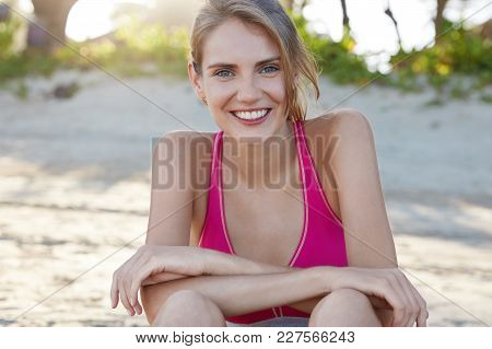 Cheerful Young Female Athlete Rests After Yoga Practice At Beach, Has Healthy Skin And Pleasant Appe