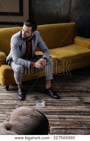 Fashionable Elegant Man With Cigar And Ashtray Sitting On Couch