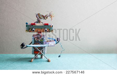Robot With Steam Iron On The Board. Gray Wall Green Floor Room Interior. Creative Design Toys Housew