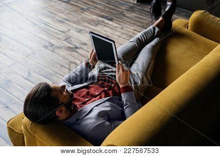 Stylish Man Using Digital Tablet While Lying On Sofa