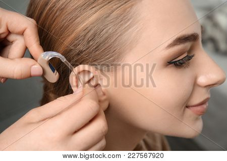 Doctor putting hearing aid in woman's ear indoors